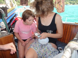Sophia and Marike scraping coconut out of a shell.