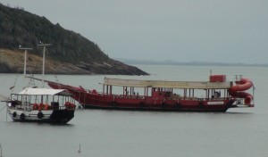 """Party Boat with Red """"Super Tube"""" attached to the rear."""